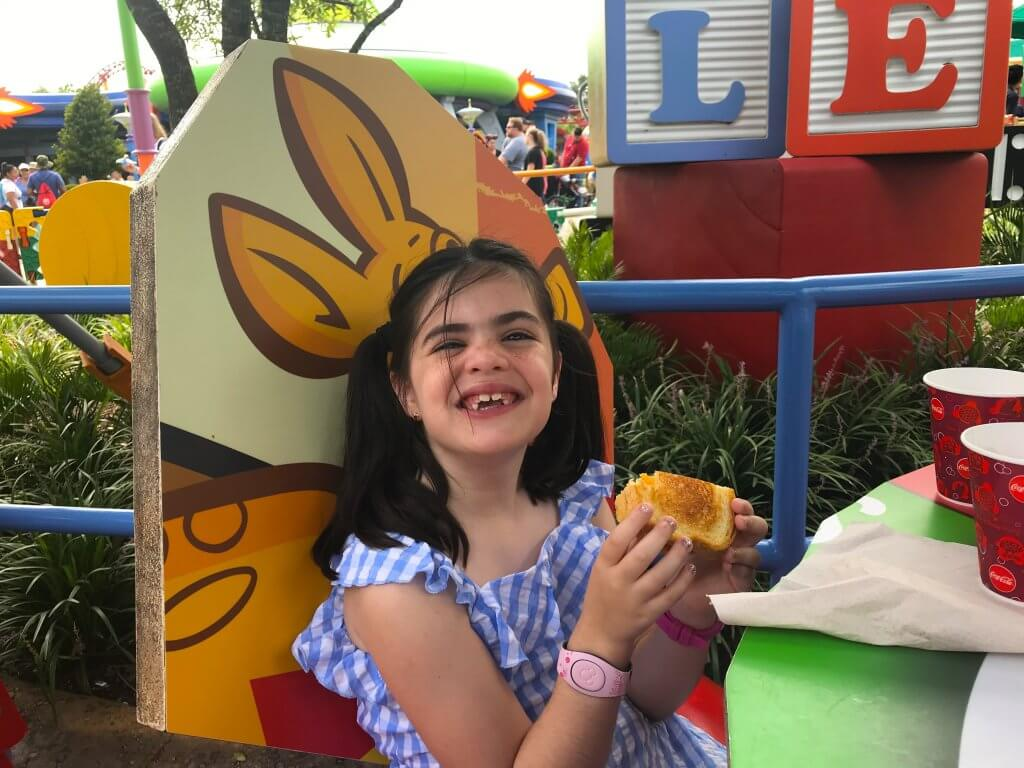 My daughter enjoying the Three-Cheese Sandwich in Toy Story Land at Walt Disney World.